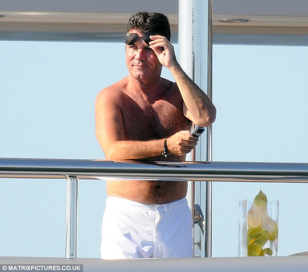 Peek-a-boo: Cowell lifted his sunglasses to get a better view of something in the distance