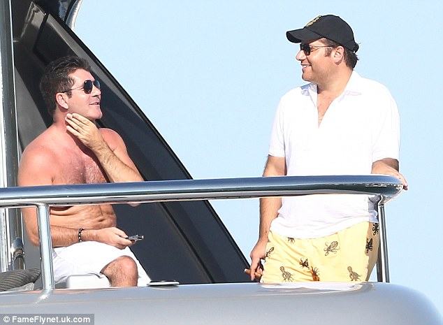 Not alone: Cowell was seen chatting to a male friend aboard the yacht