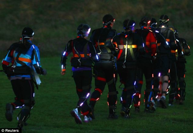 A few of the hundreds of runners in their light suits running over Arthur's Seat during the rehearsal performance