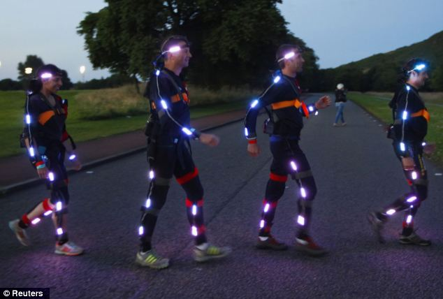 Runners walk across a path in their light suits in preparation for tonight's spectacular light display across the city