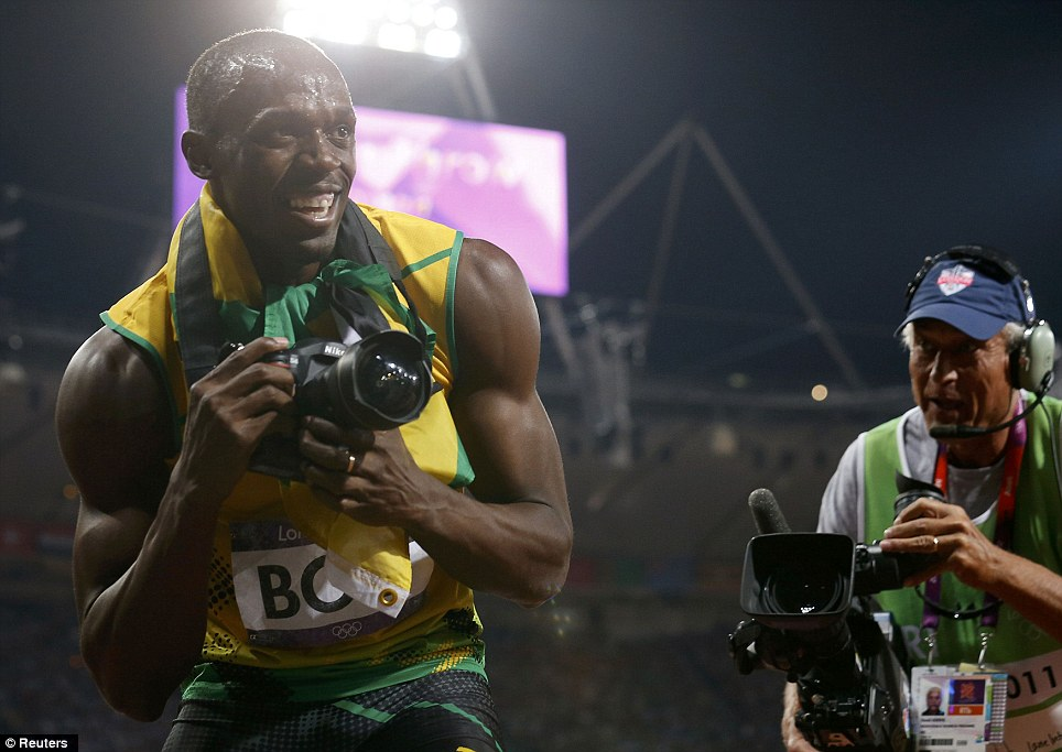Grinning: The double gold medal winner grabbed a photographer's camera and started taking snaps of the crowd