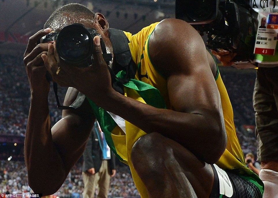 Mr charisma: As thousands of cameras flashed around the stadium, Bolt grabbed a snapshot of his own