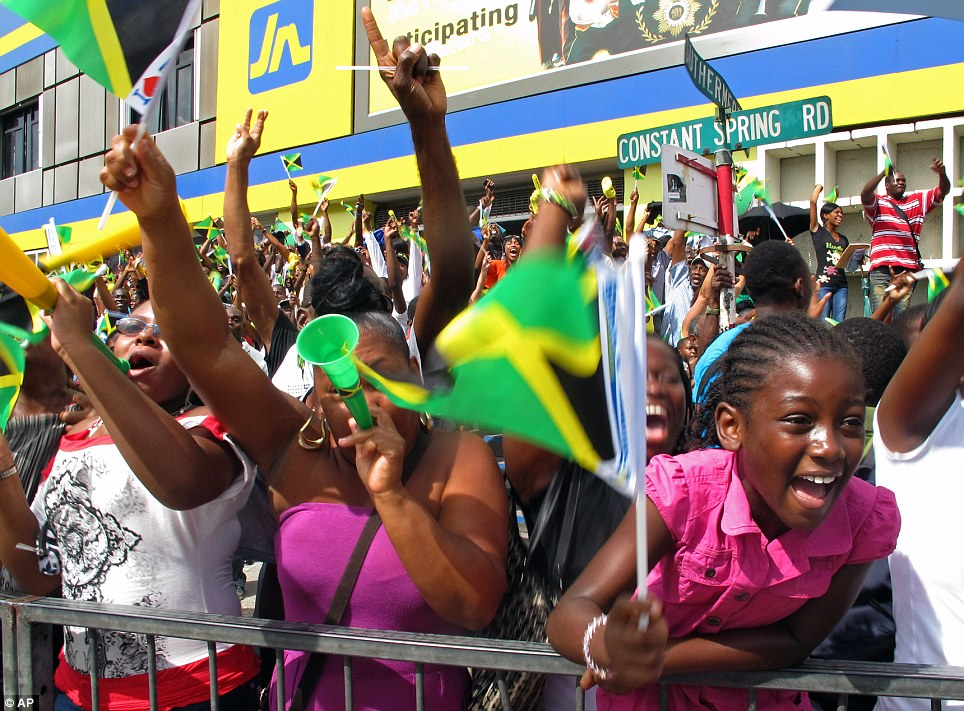Proud: Fans back home in Jamaica scream with joy as they watch their nation complete a 1-2-3 in the 200m