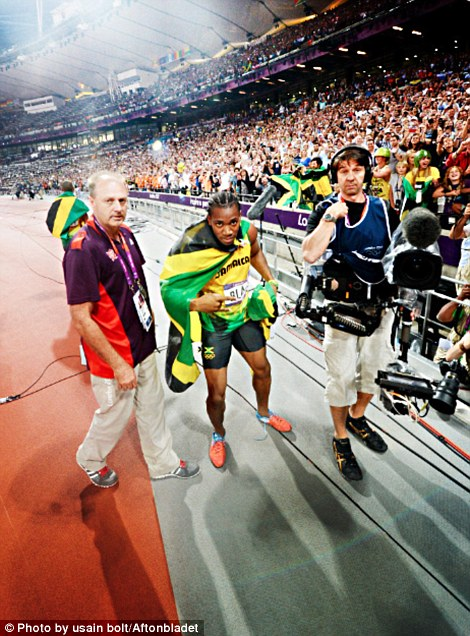 Usain Bolt using photographer Jimmy Wixtr's camera who was covering the Olympics for Swedish paper Aftonbladet.