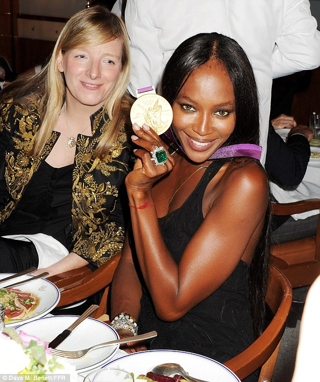 Worth her weight in gold: Naomi got a closer look at a winner's medal as designer Sarah Burton watched on from her seat