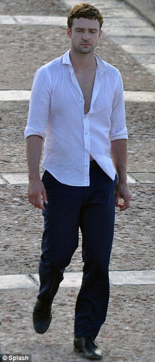 Muy caliente: The 31-year-old actor-turned-singer's shirt had only three buttons fastened, which might have also had something to do with the 88-degree temperatures happening on the San Juan set of the thriller