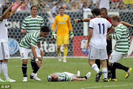 Worrying: Celtic's Dylan McGeough lies on the ground ofter a clash