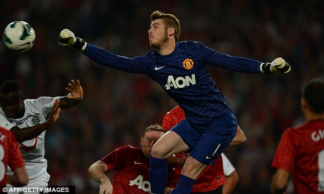 Packing a punch: United keeper David De Gea clears the ball from danger