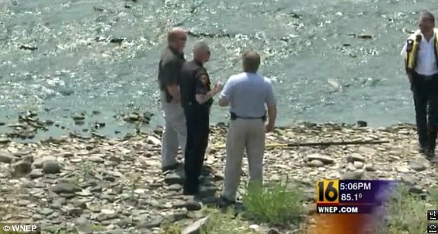 Williamsport Police Captain Michael Orwig (second left) confers with members of the Lycoming County Coroner's office at the river's edge