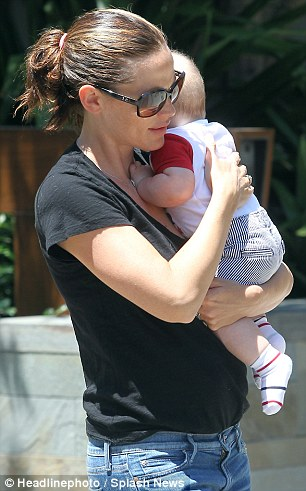 Fuss-free: Ben's wife of seven years flaunted her shrinking figure in a black v-neck t-shirt and loose-fitting blue jeans as she cradled six-month-old Samuel, whose head has already sprouted a bit of hair