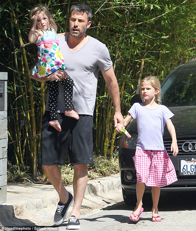 Family fun: Three-year-old Seraphina went dotty in a cute floral-and-polka-dot ensemble while her older sister Violet clutched a slice of watermelon in her lavender t-shirt and a pink gingham skirt