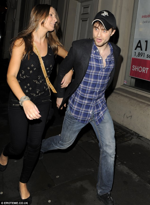 Only got eyes for Radcliffe: The mystery girl can't stop gazing at the actor as they walk past photographers