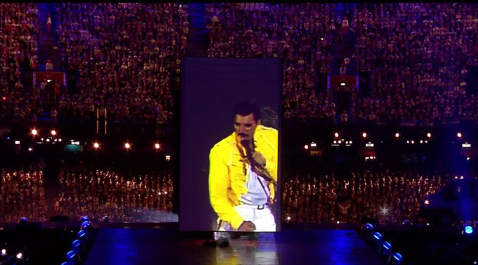 From beyond the grave: The late Freddie Mercury, on a giant screen, leads Queen out onstage for their performance at the closing ceremony