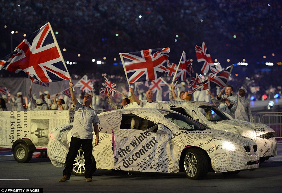 Artists wave Union Jack flags as they perform with cars, wrapped in newspaper, as the closing ceremony gets underway