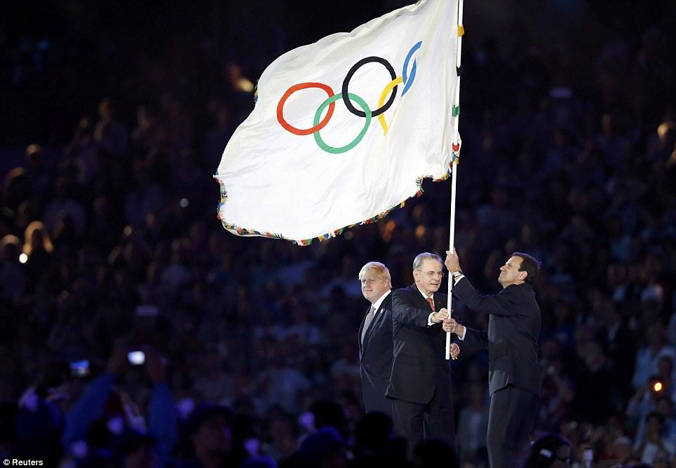 London mayor Boris Johnson passes the Olympic Flag to Rio de Janeiro Mayor Eduardo Paes, helped by IOC president Jacques Rogge