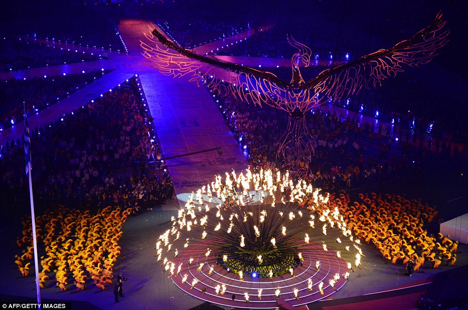 As the flames in the Olympic cauldron get weaker, the phoenix flies higher over the crowd in the stadium below