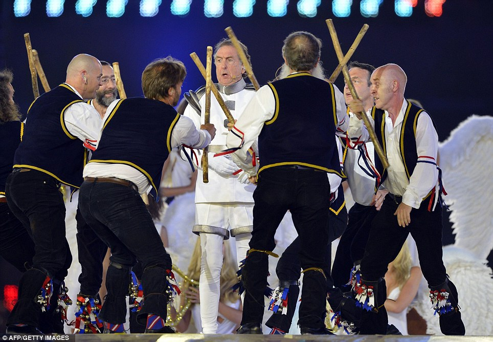 Monty Python's Eric Idle tussles with a band of morris dancers as he performs to the 80,000-strong crowd inside the Olympic Stadium