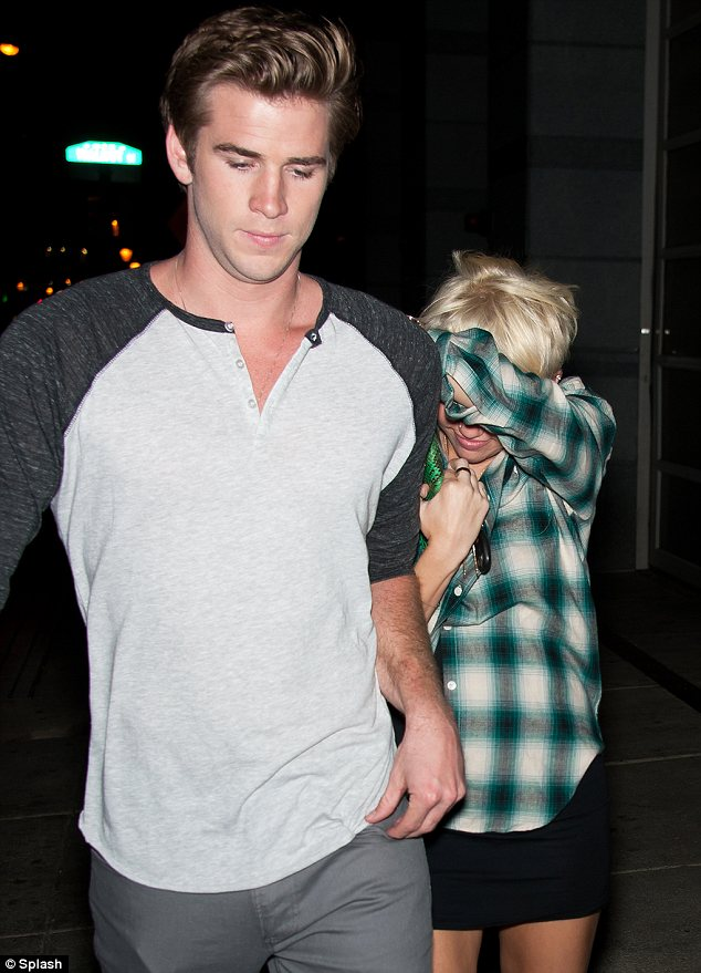 Shy moment: Miley didn't seem to want to show off her locks in Philadelphia with her fiance Liam Hemsworth yesterday