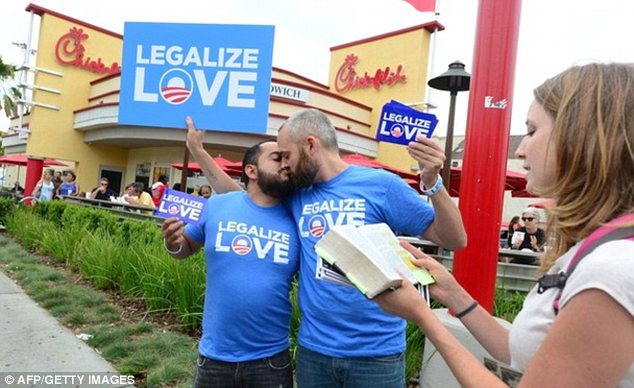 Protests: Eduardo Cisneros, left, and Luke Montgomery, centre, kiss in front of a Chick-fil-A in Hollywood as Christian activist Alicia Daberkow, right, reads the bible in one of many demonstrations outside its restaurants