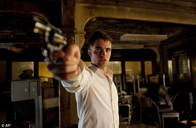 Gun-toting: Brooding: Pattison in his new film Cosmopolis in which he plays a young billionaire, Eric Packer