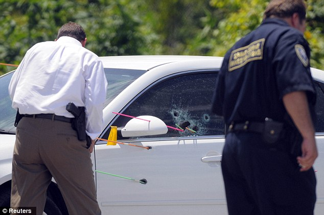 Louisiana Sheriff's Department investigators survey the crime scene of an car with apparent bullet holes in the driver's door and window after an early morning shooting at a refinery plant parking lot in LaPlace, Louisiana