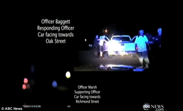 Footage: The officer leads Carter, who is not yet handcuffed, toward the patrol cars and then out of the frame
