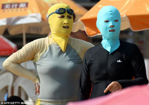 Stay away from the sun: Chinese beachgoers wearing body suits and protective head masks