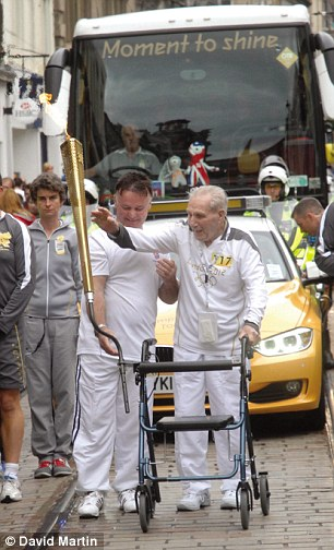Determined: Andy Coogan, despite his frailty, carried the Olympic flame in his home town in Scotland
