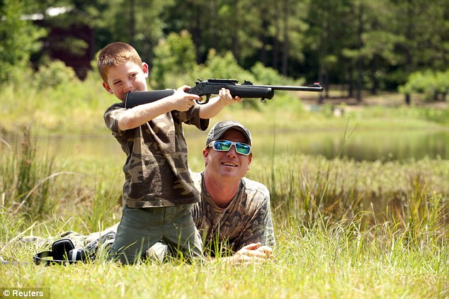 Training: Jeremy Chavez, right, helps son Ryan, 6, left, with target practice before the wild hog hunt