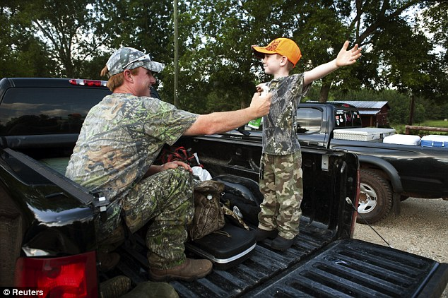 Smell: Jeremy Chavez sprays odor elimination on his son Ryan Chavez, 6, to combat the boars' strong sense of smell