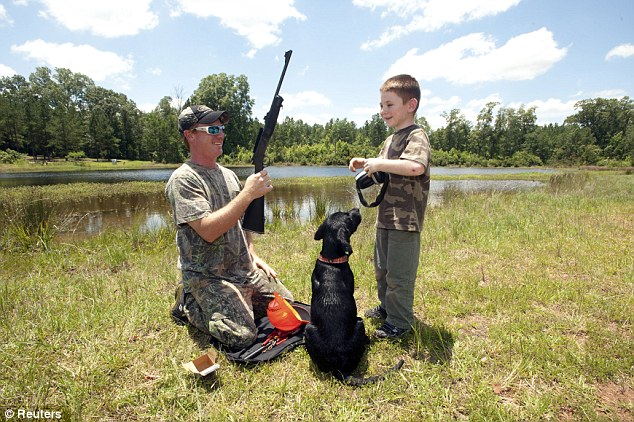 Smiles: Father, son and their dog prepare for the shoot at Great Southern Outdoors Wildlife Plantation in Union Springs, Alabama