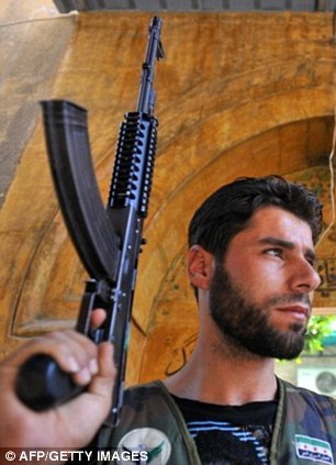 A rebel  fighter at a gate in the old city of Aleppo