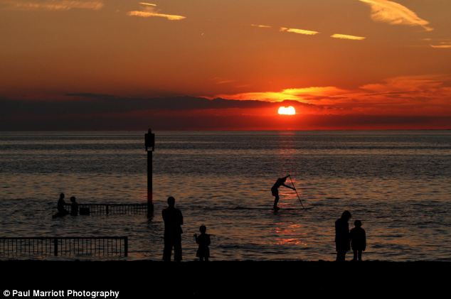 Breathtaking view: Bystanders watch the gorgeous scene as a paddleboarder balances on the sea in front of the disappearing sun