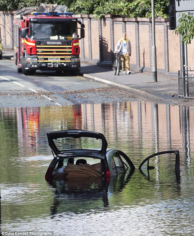 Deluge: A car encounters problems in St Helens, Merseyside, following heavy downpours and flash flooding in the Peasly Cross area of the town