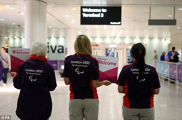 Warm welcome: Paralympic volunteers wait for the athletes to arrive at Heathrow