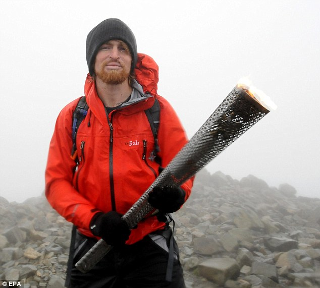 Hot stuff: Karl Hinett holds the English Paralympic flame at the top of Scafell Pike, England's highest peak