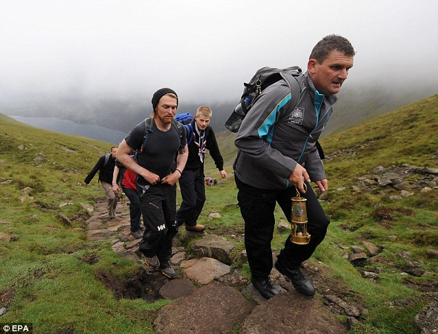 Scaling new heights: Mark Edwards (front), of the Torch Security Team, carries a lantern to the top of Scafell Pike with torchbearer Karl Hinett and scouts