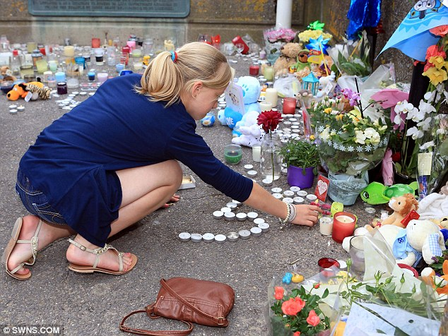 Candle: A woman adds to the tributes to Dylan Cecil left on the seafront at Burnham-on-Sea, Somerset