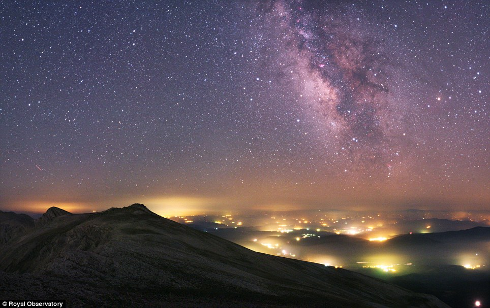 The Milky Way stretches across the sky above the manmade pockets of hazy lights from the towns and villages below near Uludag National Park in Turkey