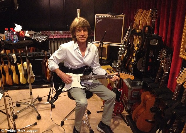 'Had fun in the Paris studio': Sir Mick uploaded a picture to his Twitter account of himself holding a guitar