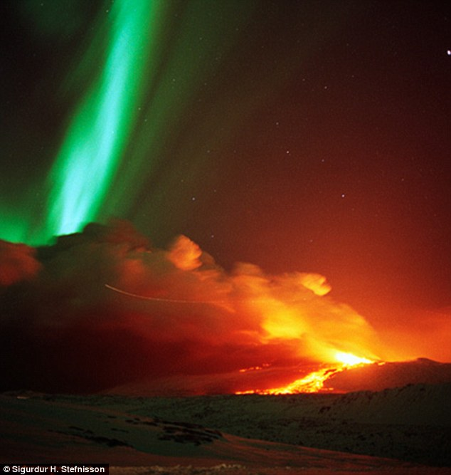 Stunning: Photography from Iceland shows us a vivid landscape of red and green, as lava flows underneath the Northern Lights