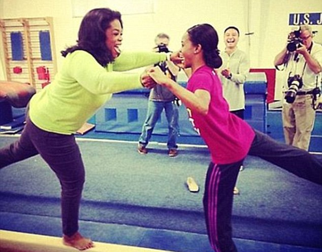 Playful: Oprah tried out the balance beam, helped by Gabby