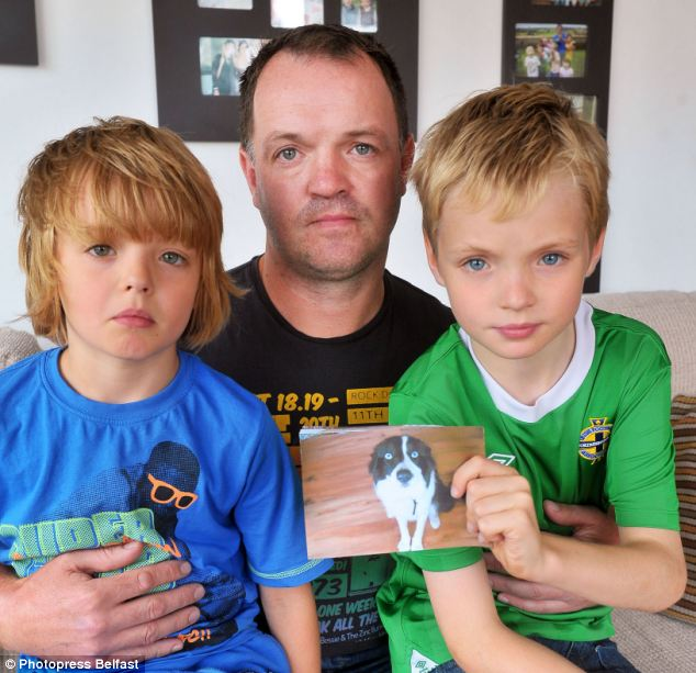 Devastated owners: Martin Agnew with his sons Jake, 6, left, and Justin, 10, holding a photograph of their dog Cody as a puppy