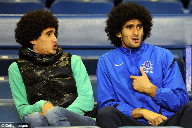 Day off: Everton midfielder Marouane Fellaini (right) sits with his brother in the Goodison Park stands