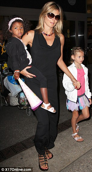 Jet set: Heidi and her brood were spotted arriving back in Los Angeles tonight, seen here carrying Lou and holding hands with Leni