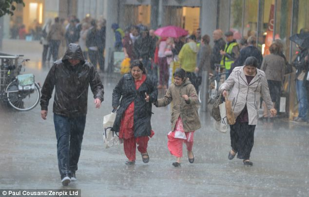 Suddenly torrential: Shoppers were caught out in the wet weather today as a downpour drenched Manchester