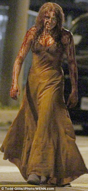 Dressed up: The images show the moment after she is covered in pigs blood by her high school colleagues at her school prom