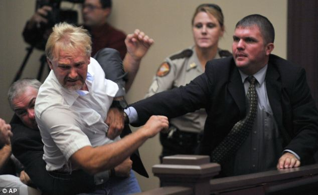 Anger: Wesley Thomas, whose stepdaughter was shot dead by three soldiers last December, is tackled by courtroom security during the hearing of one of her murderers