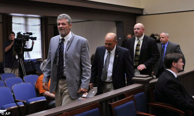 Heartbreak: Brett Roark is escorted out by courtroom security during the hearing of a defendant