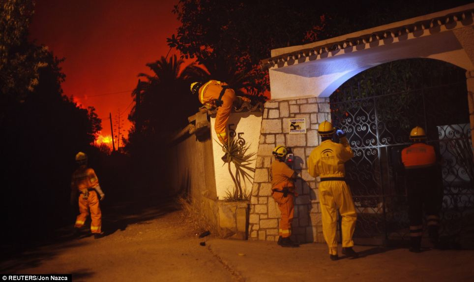 Rescue workers look for people inside a chalet as the fire rages